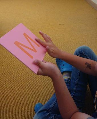 Buchstaben aus Schmirgelpapier werden nachgefahren, um ihre Form zu verinnerlichen.